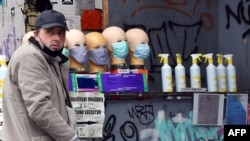 A grey market salesman sells face masks and hand sanitiser at a street corner in Sarajevo, on April 22, 2020. - Grey market of sanitation products is increasingly present as Bosnia reaches numbers of 1400 cases of infection by new corona virus …