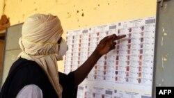 Seorang pemilih yang mengenakan masker memeriksa data pemilih di sebuah tempat pemungutan suara di Gao, Mali, 29 Maret 2020.