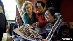 Para peserta reuni keluarga dari Korea Selatan melihat-lihat foto lama di sebuah hotel yang digunakan sebagai tempat menunggu di Sokcho, Korea Selatan (19/10). (Reuters/Kim Hong-Ji)