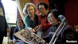 等待和亲人团聚的韩国公民10月19日在束草市宾馆查看旧照。