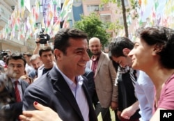 FILE - Greeted by supporters, Selahattin Demirtas, leader of pro-Kurdish Peoples' Democracy Party, smiles as he arrives at his party headquarters in Ankara, Turkey, June 9, 2015.