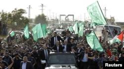 Pemimpin Hamas Khaled Meshaal (kiri), bersama pemimpin senior Hamas Ismail Haniyeh (kanan) malakukan pawai dan melambaikan tangan kepada para pendukungnya setibanya di Gaza (7/12). Warga Palestina memperingati 25 tahun berdirinya kelompok militan Islamis Hamas, hari ini.