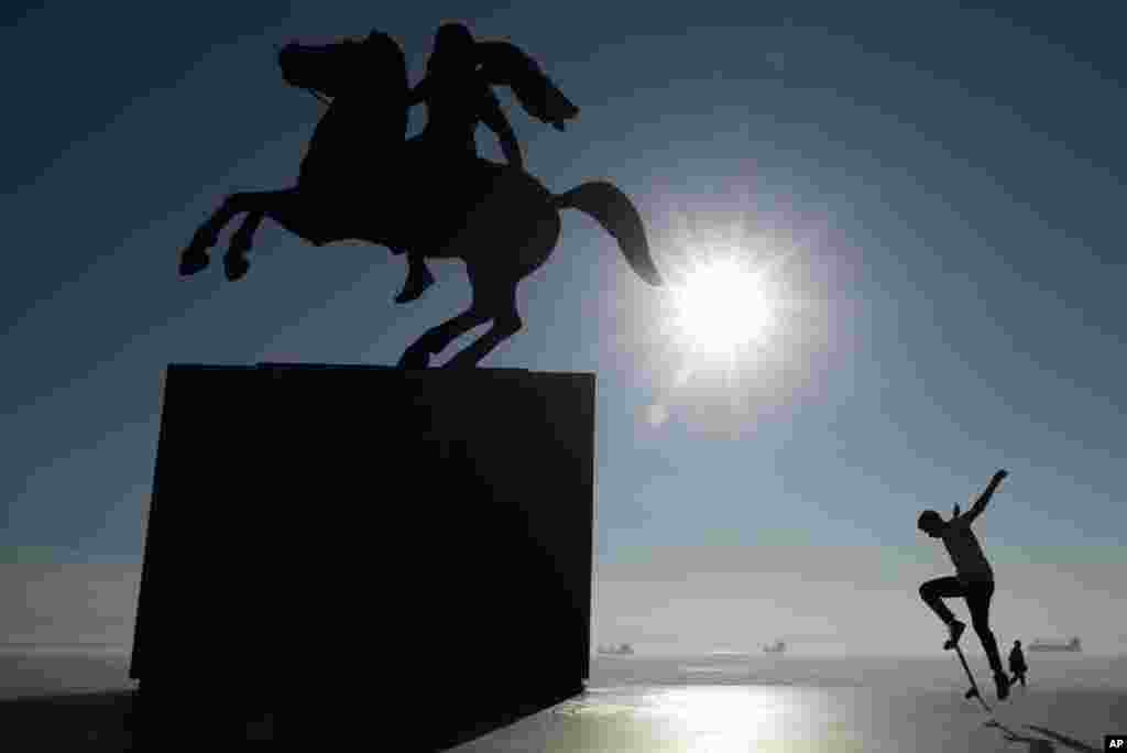 A skateboarder practices near the modern bronze statue of Alexander the Great on his famous horse Bucephalus in the northern port city of Thessaloniki , Greece.