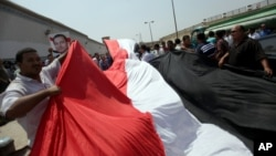 Supporters of Egypt's deposed president Hosni Mubarak wave a large national flag in front of Torah Prison in Cairo, Aug. 22, 2013.