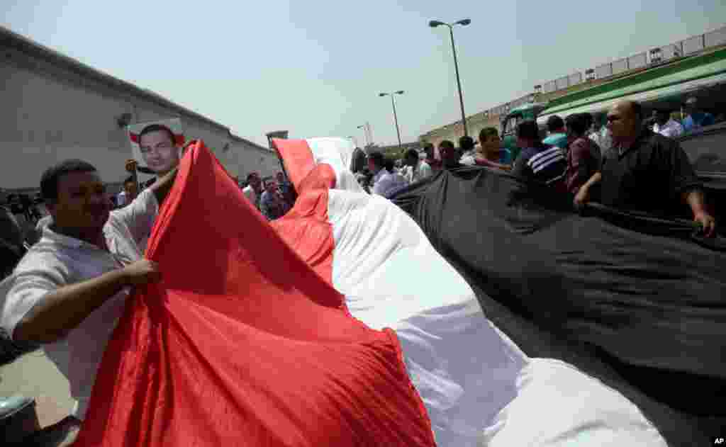 Supporters of Egypt's deposed president Hosni Mubarak wave a large national flag in front of Torah Prison in Cairo, August 22, 2013.
