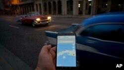 Un ciudadano cubano observa un mapa de la Isla en una aplicación móvil, en las calles de La Habana, el 21 de febrero de 2019.