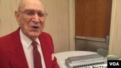 Jack Hopkins with his harmonica cake as he turned 97 years old at the Virginia Harmonica Fest. (C/ Presutti/VOA)