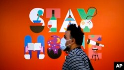 A man wearing a face mask walks in front of a poster recommending people to stay at home, at a department store in Berlin, Germany, April 20, 2020.