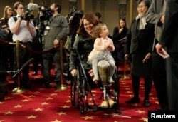 Senator Tammy Duckworth (D-IL) carries her daughter Abigail during a mock swearing in with U.S. Vice President Joe Biden during the opening day of the 115th Congress on Capitol Hill in Washington, Jan. 3, 2017.