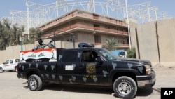 Iraqi security forces guard the entrance to a sports complex being built by a Turkish construction company, in the Shi'ite district of Sadr City, Baghdad, Sept. 2, 2015.