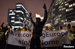 A man raises his hands during a protest in support of a new EU migration policy, a day before an EU leaders' meeting, in Brussels, Belgium, Dec. 13, 2017.