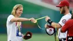Olympic gold medal swimmer Katie Ledecky, left, hands her medals to Washington Nationals' Bryce Harper, right, to hold before she threw out the ceremonial first pitch before a baseball game between the Baltimore Orioles and the Washington Nationals, Aug. 24, 2016, in Washington, D.C.