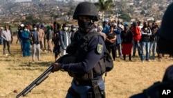 一名南非武裝警察在警察部長貝基·塞萊訪問鳳凰城時巡邏。鳳凰城是南非德班市附近的一個受到動亂和種族緊張局勢嚴重影響的社區。(2021年7月17日)