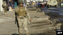 Иракский солдат охраняет место взрыва на багдадском рынке
