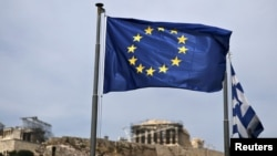Bendera Uni Eropa berkibar dengan latar belakang kuil kuno Parthenon di Athena, Yunani (Foto: dok). Athena tengah berupaya membujuk para kreditor Eropa untuk meneruskan pinjaman yang dibutuhkan guna menghindarkan kegagalan membayar hutang.
