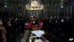 Seorang wanita mencium layar pelindung di atas peti mati Patriark Irinej saat dia berbaring di gereja Kongregasional di Beograd, Serbia, Sabtu, 21 November 2020. (Foto: AP)