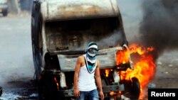 Kudüs'teki çatışmada yakılan bir İsrail aracı önünde duran Filistinli bir gösterici