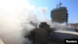 Smoke rises from the site of a bomb attack near Khullani Square in Baghdad, Feb. 5, 2014.