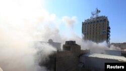 浓烟从巴格达库拉尼广场附近的一处炸弹袭击现场升起。(2014年2月5日)