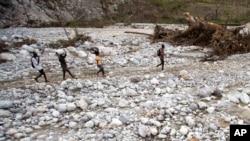 Des résidents marchent près de la rivière Bois Droit, à Port-a-Piment, le 18 octobre 2016 à Haïti.