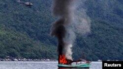 Perahu nelayan Vietnam yang tak berawak diledakkan oleh angkatan laut Indonesia, dan tenggelam di lepas pantai Natuna di Anambas, Kepulauan Riau, 5 Desember 2014. (Foto: REUTERS / Antara Foto / Immanuel Antoneus).