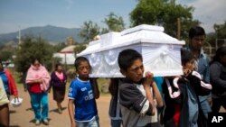 Cousins carry a coffin with the body of 6-year-old Victor Serrano Ruiz in the village of San Isidro, Puebla State, Mexico, May 10, 2017.