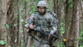 In a May 9, 2012 photo, Capt. Sara Rodriguez of the 101st Airborne Division walks through the woods during the expert field medical badge testing at Fort Campbell, Ky., on May 9, 2012.