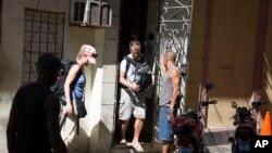 Turistas salen de una vivienda privada de alquiler en La Habana, Cuba.