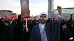 A Muslim cleric chants slogans alongside women in a rally to protest the execution by Saudi Arabia last week of Sheikh Nimr al-Nimr, a prominent opposition Saudi Shiite cleric, in Tehran, Iran, Jan. 4, 2016. (AP Photo/Vahid Salemi)