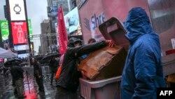 Seorang pria sedang membuang sampah di Times Square, New York, 28 Desember 2018. (Foto: AFP)