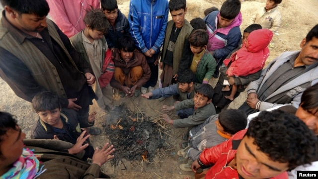 Internally displaced Afghan men and children warm themselves around a fire at a refugee camp on the outskirts of Kabul, December 12, 2012.