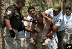 A Central American migrant is detained by Mexican immigration agents on the highway to Pijijiapan, Mexico, April 22, 2019.