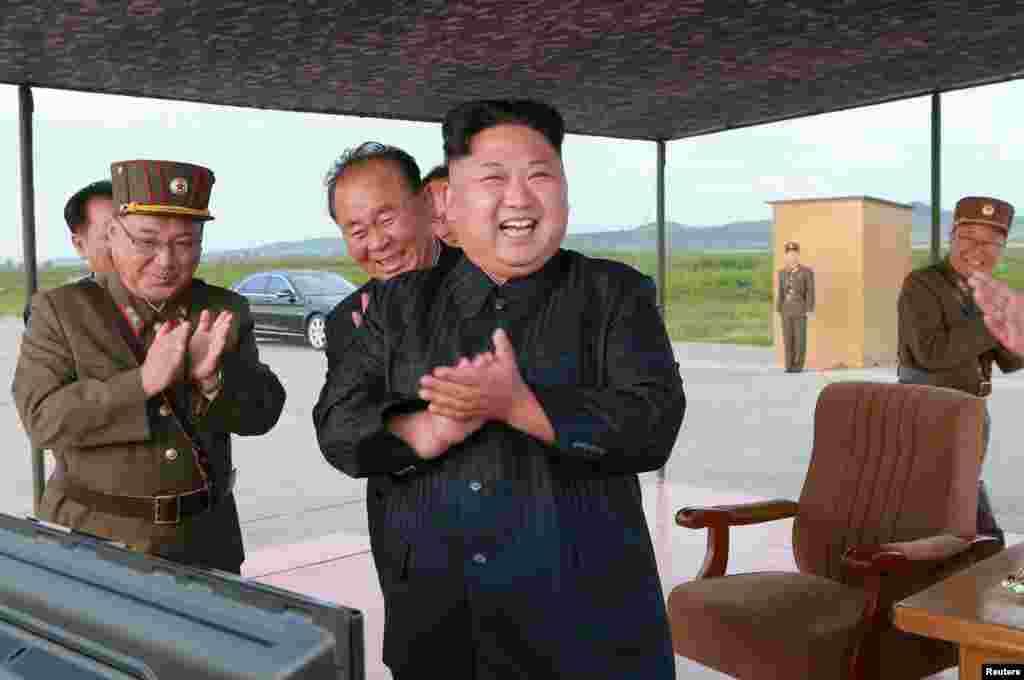 김정은 북한 국무위원장(가운데)과 군 간부들이 화성-12 발사장면을 보며 박수치고 있다.