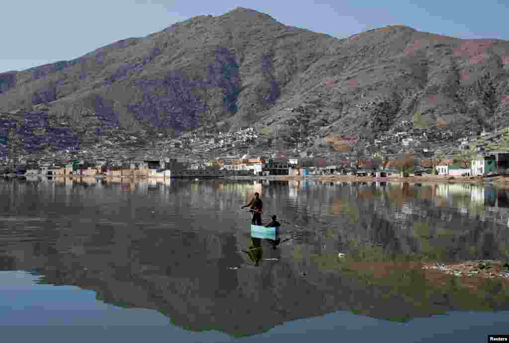Afghan men row a raft on a lake in Kabul, Afghanistan.