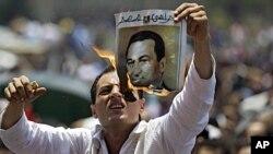 开罗数百示威者举行集会,一名抗议者焚烧前总统穆巴拉克的照片