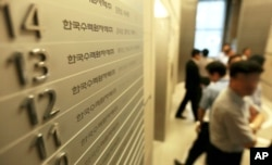 FILE - Employees of Korea Hydro & Nuclear Power Co. walk inside the company's Seoul office, which in 2014 faced a cyberattack in which hackers stole and released information.