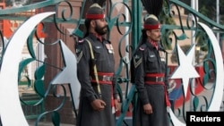FILE - Pakistani Rangers take part in the daily flag lowering ceremony at the India-Pakistan joint border at Wagah some 20 km (12 miles) to the east of Lahore.