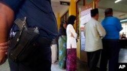 Polisi Malaysia siaga di sebuah TPS saat warga memberikan suara dalam pemilu di Pekan, negara bagian Pahang (foto: ilustrasi).