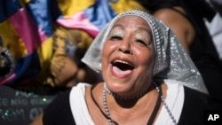 "A reveler dressed as nun sings and dances during the ""Carmelitas"" carnival parade in Rio de Janeiro, Brazil, Feb. 13, 2015."