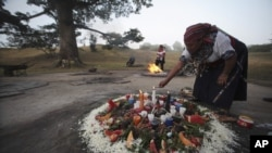 An indigenous woman prepares a sacred fire during the Oxlajuj Batz ceremony to celebrate the end of the Maya calendar in the ceremonial center of Kaminal Juyu in Guatemala City, December 12, 2012.