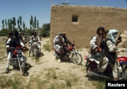 FILE - Taliban fighters ride on motorbikes in an undisclosed location in Afghanistan, July 14, 2009.