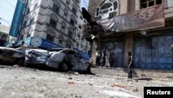 也門民眾駐足觀看薩那街頭被毀掉的胡賽反叛武裝與忠於前總統薩利赫的武裝相撞的車輛 (2017年12月5日)