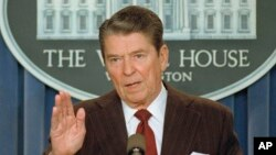 FILE - U.S. President Ronald Reagan talks with reporters in the White House briefing room, Nov. 25, 1986.