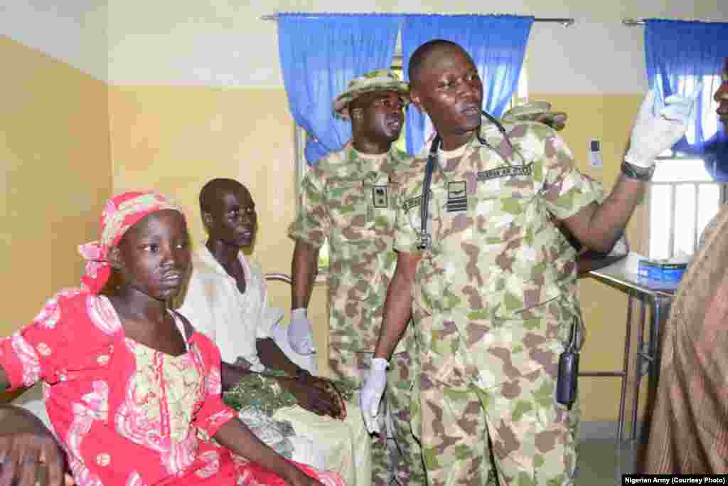 Nigerian military personnel speak to Amina Ali after her rescue.