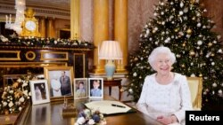 Britain's Queen Elizabeth sits at a desk in the 1844 Room after recording her Christmas Day broadcast to the Commonwealth, in Buckingham Palace, in this undated photograph received in London, Dec. 24, 2017.