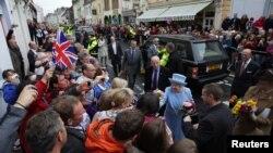 Ratu Elizabeth II (tengah) bersama Pangeran Philip disambut meriah oleh warga di kota Ennniskillen, Irlandia Utara (26/6).