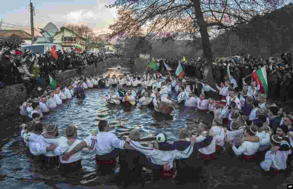 Bulgarians sing, play bagpipes and chain dance in the icy waters of the Tundzha river during Epiphany, in Kalofer.