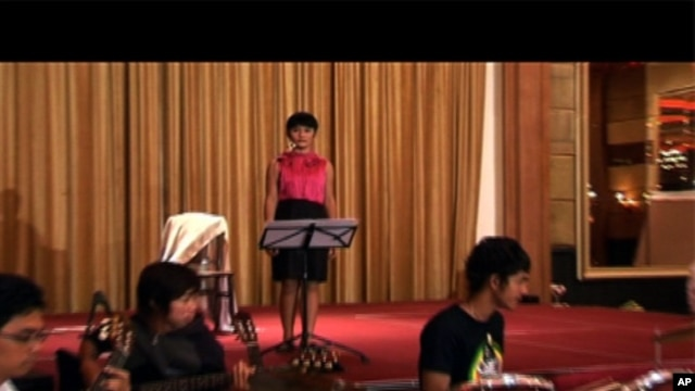 Panh Bosba practices singing with her band.