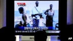 韩国人观看电视转播1月21日韩国部队夺回被挟持货轮的报道