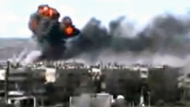 This video image taken from amateur video and broadcast by Bambuser/Homslive shows a series of devastating explosions in the central Syrian city of Homs, Syria, June 11, 2012.